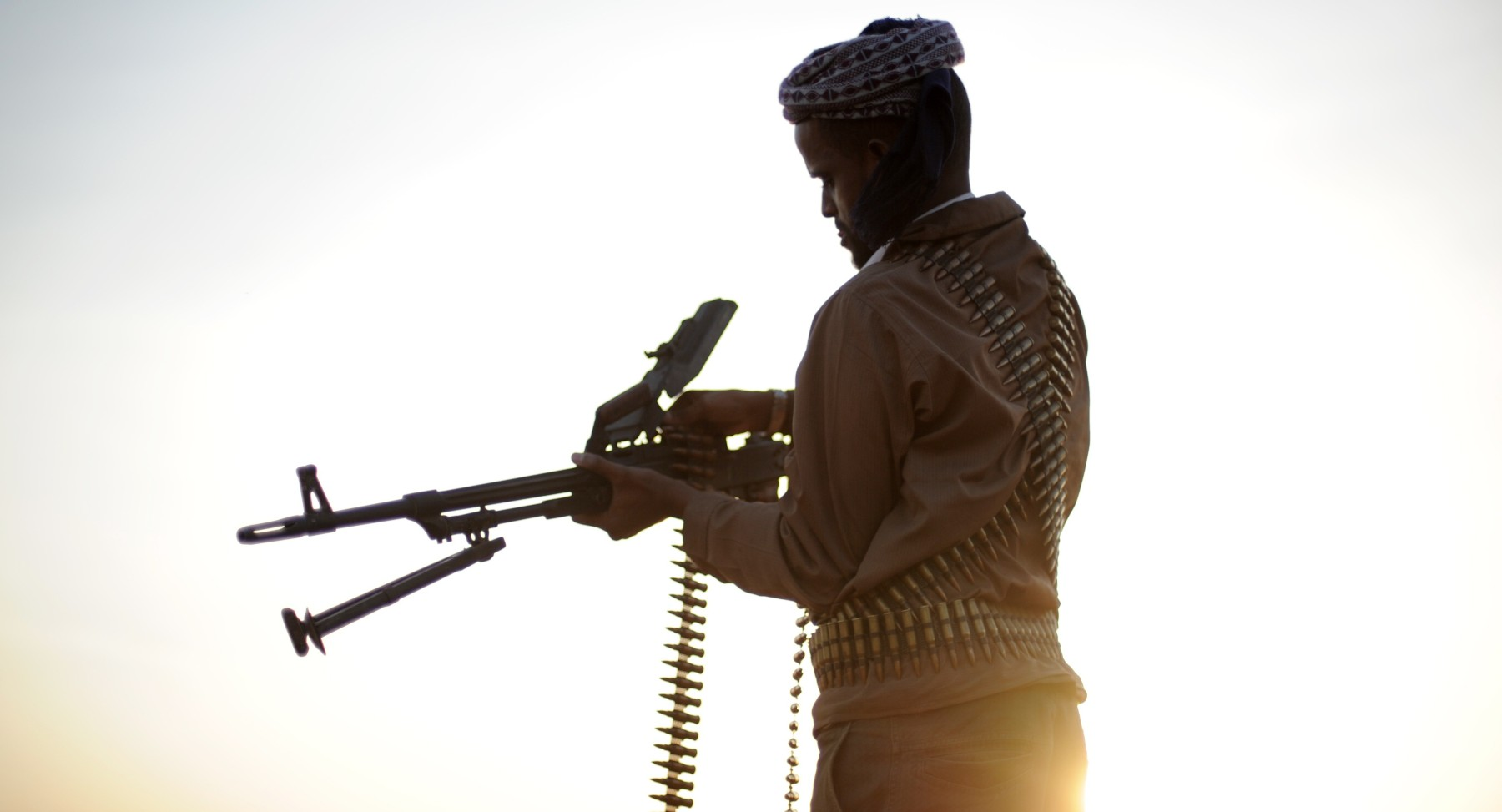 TO GO WITH AFP STORY BY JEAN-MARC MOJON A pirate loads his high caliber weapon in the early morning in the semi-desertic plains near the central Somalia town of Galkayo on August18, 2010. Fighting a losing battle against the sand that has already completely covered the old Italian port, Hobyo's scattering of rundown houses and shacks looks anything but the nerve centre of an activity threatening global shipping. Hobyo pirates have collected millions of dollars in ransoms over the past two years. They even have currency checking and counting machines for the bags of air-dropped cash they receive. AFP PHOTO / ROBERTO SCHMIDT (Photo credit should read ROBERTO SCHMIDT/AFP/Getty Images)