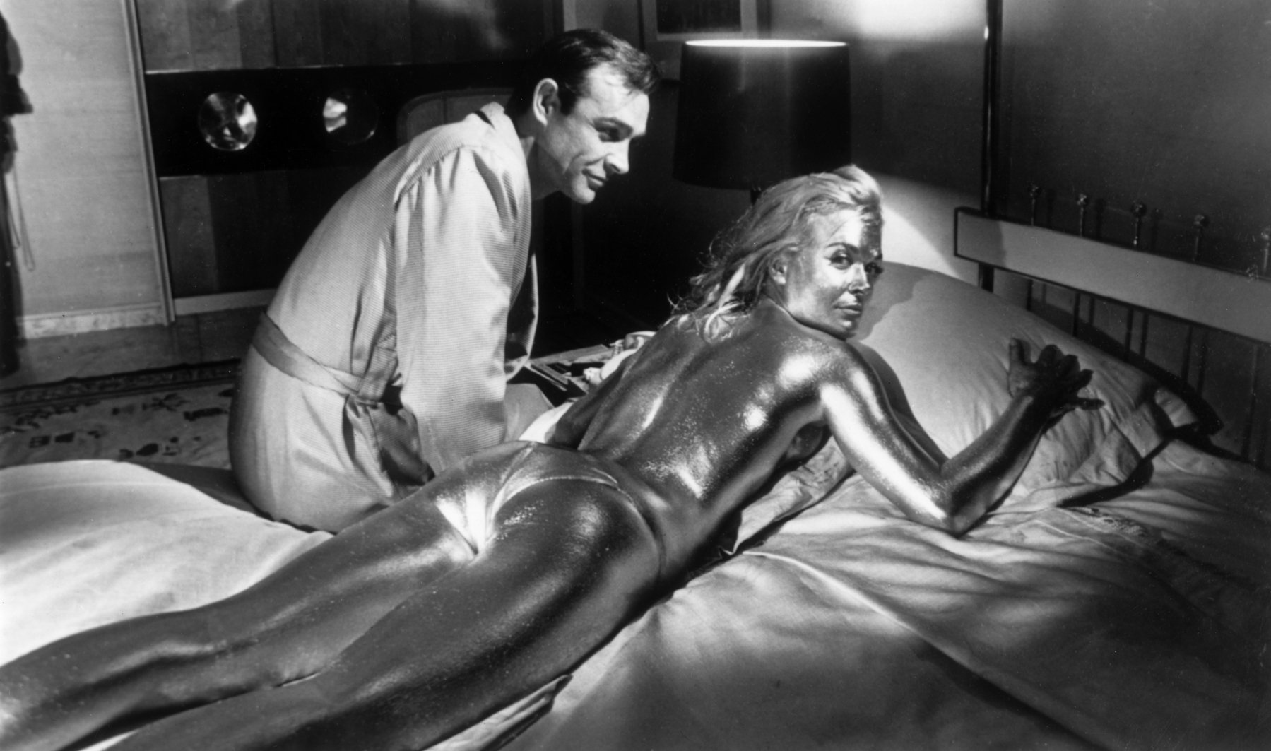 21st April 1964:  Sean Connery sitting beside his co-star English actress, Shirley Eaton, covered in gold during the filming of a scene from the James Bond film 'Goldfinger', directed by Guy Hamilton.  (Photo by Keystone/Getty Images)