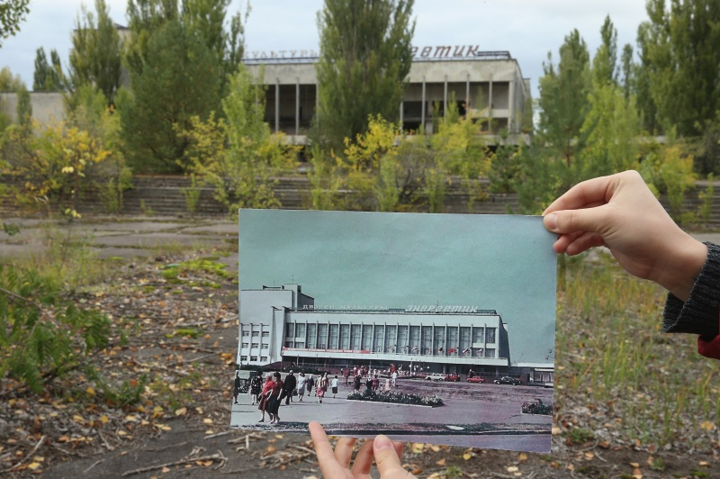 "PRIPYAT, UKRAINE - SEPTEMBER 29: An assistant holds up a photo showing the city of Pripyat's main square and the ""Energetik"" cultural center before 1986 at the same site that today is abandoned and overgrown with trees on September 29, 2015 in Pripyat, Ukraine. Pripyat lies only a few kilometers from the former Chernobyl nuclear power plant and was built in the 1970s to house the plant's workers and their families. On April 26, 1986, technicians at Chernobyl conducting a test inadvertently caused reactor number four to explode, sending plumes of highly radioactive particles and debris into the atmosphere. Authorities evacuated 120,000 people from the area, including 43,000 from Pripyat. Today Pripyat is a ghost-town, its apartment buildings, shops, restaurants, hospital, schools, cultural center and sports facilities derelict and its streets overgrown with trees. The city lies in the inner exclusion zone around Chernobyl where hot spots of persistently high levels of radiation make the area uninhabitable for thousands of years to come. (Photo by Sean Gallup/Getty Images)"