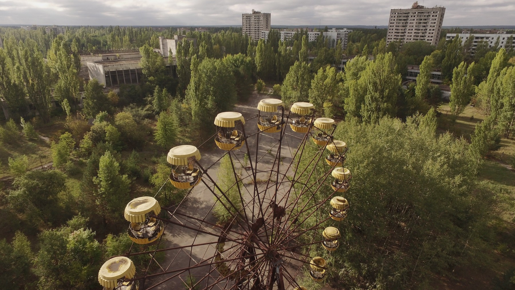 PRIPYAT, UKRAINE - SEPTEMBER 30:  In this aerial view an abandoned ferris wheel stands on a public space overgrown with trees in the former city center on September 30, 2015 in Pripyat, Ukraine. Pripyat lies only a few kilometers from the former Chernobyl nuclear power plant and was built in the 1970s to house the plant's workers and their families. On April 26, 1986, technicians at Chernobyl conducting a test inadvertently caused reactor number four to explode, sending plumes of highly radioactive particles and debris into the atmosphere. Authorities evacuated 120,000 people from the area, including 43,000 from Pripyat. Today Pripyat is a ghost-town, its apartment buildings, shops, restaurants, hospital, schools, cultural center and sports facilities derelict and its streets overgrown with trees. The city lies in the inner exclusion zone around Chernobyl where hot spots of persistently high levels of radiation make the area uninhabitable for thousands of years to come.  (Photo by Sean Gallup/Getty Images)