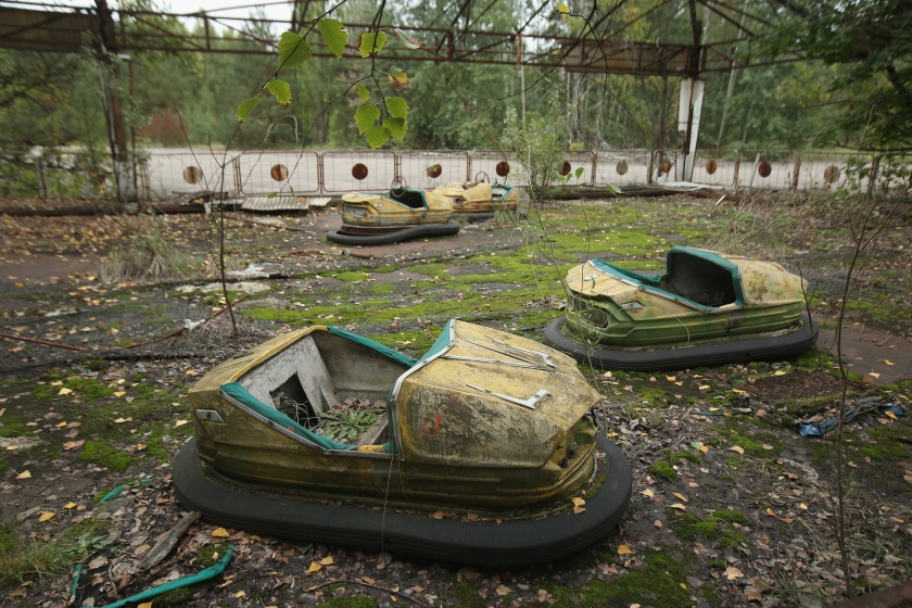 PRIPYAT, UKRAINE - SEPTEMBER 29: Bumper cars stand in an abandoned amusement park on September 29, 2015 in Pripyat, Ukraine. Pripyat lies only a few kilometers from the former Chernobyl nuclear power plant and was built in the 1970s to house the plant's workers and their families. On April 26, 1986, technicians at Chernobyl conducting a test inadvertently caused reactor number four to explode, sending plumes of highly radioactive particles and debris into the atmosphere. Authorities evacuated 120,000 people from the area, including 43,000 from Pripyat. Today Pripyat is a ghost-town, its apartment buildings, shops, restaurants, hospital, schools, cultural center and sports facilities derelict and its streets overgrown with trees. The city lies in the inner exclusion zone around Chernobyl where hot spots of persistently high levels of radiation make the area uninhabitable for thousands of years to come. (Photo by Sean Gallup/Getty Images)