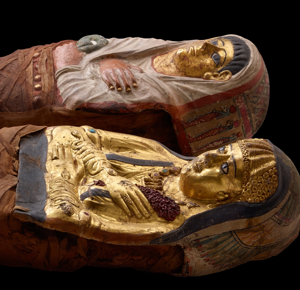 CT scanning of these two beautifully-gilded and decorated mummies of Ptolemaic Egypt revealed a young sister and brother. Both are portrayed wearing a mix of Greek fashions (like the golden girl's curls) and Egyptian fashions.