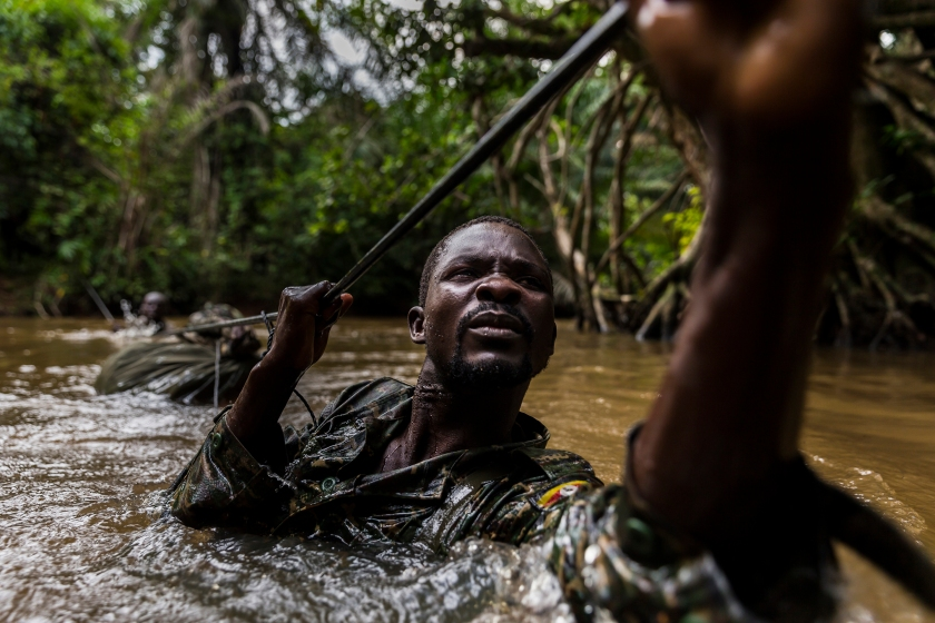 MBOKI, CENTRAL AFRICAN REPUBLIC, 25 NOVEMBER 2014: Ugandan soldiers cross one of many rivers while on patrol against the Lord's Resistance Army close to the border of the DRC. The Ugandan contingent based in CAR are focused on the aprehension of the Lord's Resistance Army, LRA, the notorious rebel group led by Joseph Kony which has terrorized citizens of Uganda, C.A.R, South Sudan and the Democratic Republic of Congo for the last 4 decades. Soldiers are seen crossing a river, a technique they have perfected with ropes despite the fact that many of the men cannot swim. The LRA contingent they are hunting is coming from Garamba National Park where they have been hunting ivory, a task ordered by Joseph Kony and detailed in a commander's diary that this Ugandan contingent captured in an ambush earlier in 2014. Defectors say that Joseph Kony, leader of the LRA, is increasingly reliant on ivory as a means of trade for weapons and supplies from their hosts the Sudanese Army. World Press Photo 2016 Contest