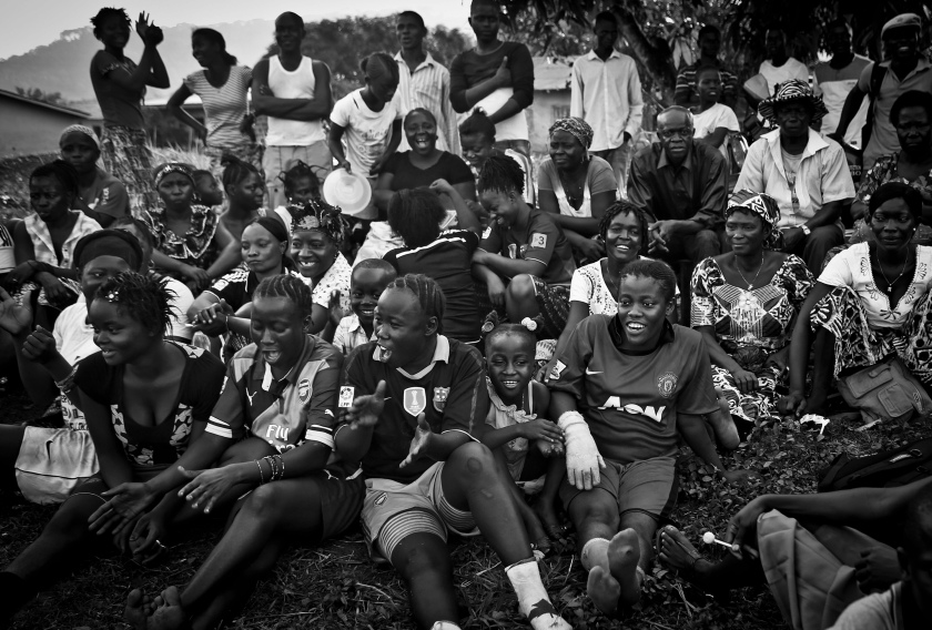 Bandu Turay, second to top row, fourth from right, watches her son Erison, not pictured, play soccer as others cheer for the Ebola Survivor's Soccer Club, on a field near their house, in the city of Kenema, 190 miles east of the capital Freetown, Sierra Leone, Tuesday, April 21, 2015. Last year, 38 members of Erison's family died from the deadly Ebola virus, which has killed over 11,000 across West Africa. Erison founded the Ebola Survivor's Soccer Club as a support network for survivors and a means to battle negative stigmas in the community. (Photo Credit/Tara Todras-Whitehill for the New York Times) World Press Photo 2016 Contest