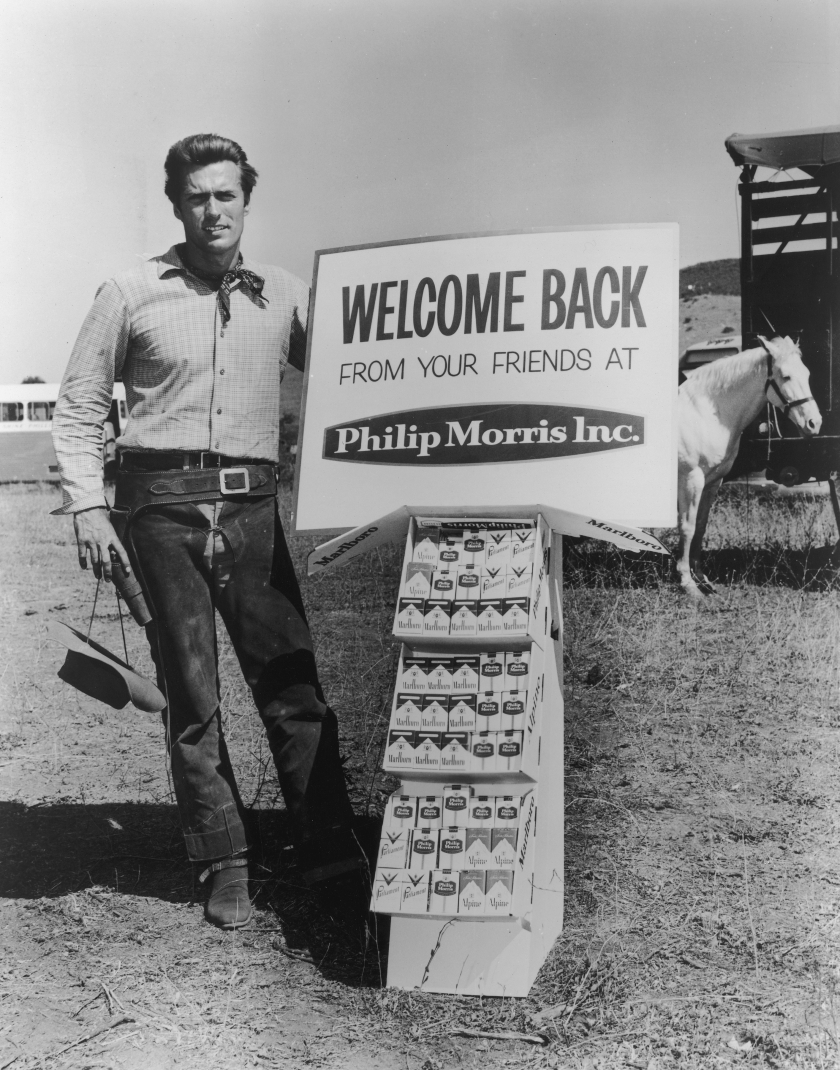 circa 1965: Full-length portrait of American actor Clint Eastwood posing in Western gear next to a display of Philip Morris tobacco products in front of a white horse on an outdoor ranch. Eastwood starred in the television series, 'Rawhide'. He wears chaps, a gun holster, and a bandana while a cowboy hat hangs by his side. (Photo by Hulton Archive/Getty Images)