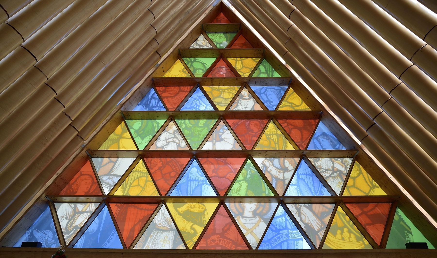 "This photo taken on December 30, 2014 shows the front window that incorporates images from Christchurch Cathedral's original rose window in Christchurch's ""Cardboard Cathedral"", designed by award-winning Japanese architect Shigeru Ban.  The structure, which is a temporary replacement for the 1881 Anglican cathedral destroyed in the February, 2011 quake with killed 185 people, is an A-frame building constructed with weather-proofed cardboard tubes.      AFP PHOTO / MARTY MELVILLE        (Photo credit should read Marty Melville/AFP/Getty Images)"