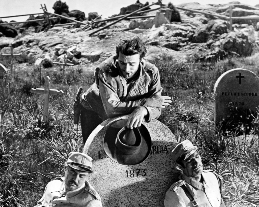 Joe, played by American actor Clint Eastwood, contemplates two dead soldiers in a graveyard in a promotional still for 'A Fistful of Dollars', directed by Sergio Leone, 1964. (Photo by Silver Screen Collection/Getty Images)