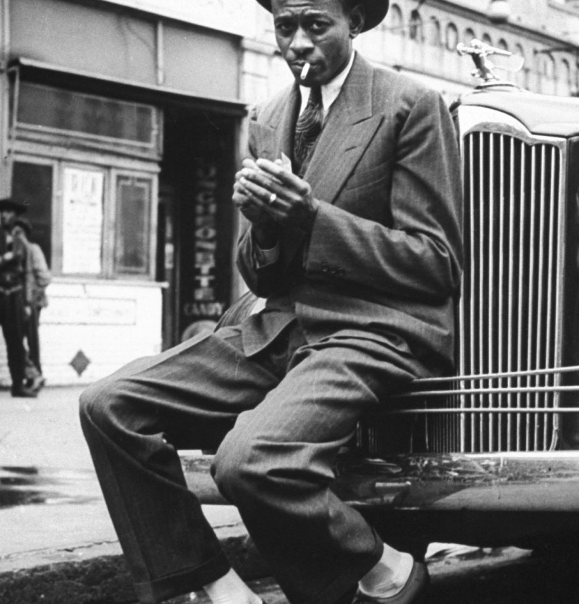 Baseball player Satchel Paige, looking dapper, lighting his cigarette while sitting on front bumper of large car. (Photo by George Strock/The LIFE Picture Collection/Getty Images)