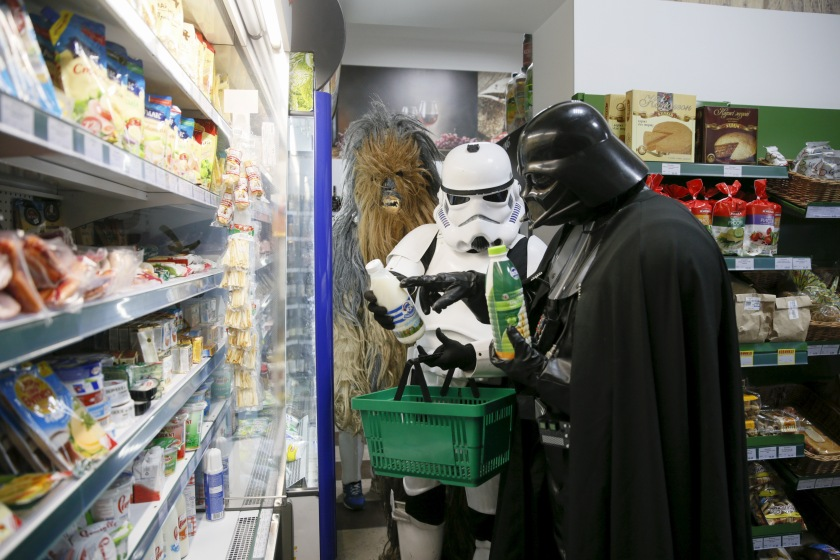 "Darth Mykolaiovych Vader (R), who is dressed as the Star Wars character Darth Vader, and people dressed as Star Wars characters Chewbacca (L) and a Stormtrooper pose for a picture as they select products in a grocery store in Odessa, Ukraine, December 3, 2015. Darth Vader was bent on galactic domination, but his Ukrainian namesake enjoys more mundane pursuits: local politics, walking the family dog and a spot of embroidery. The Ukrainian citizen, who has changed his name to Darth Mykolaiovych Vader, ran for the post of local mayor in October, his political backers dressed as Stormtroopers. In his trademark black outfit, he is a regular sight around Odessa, a major port city on southern Ukraine's Black Sea coast. REUTERS/Valentyn Ogirenko PICTURE 7 OF 22 - SEARCH ""VALENTYN VADER"" FOR ALL IMAGES TPX IMAGES OF THE DAY - RTX1Y7XM"