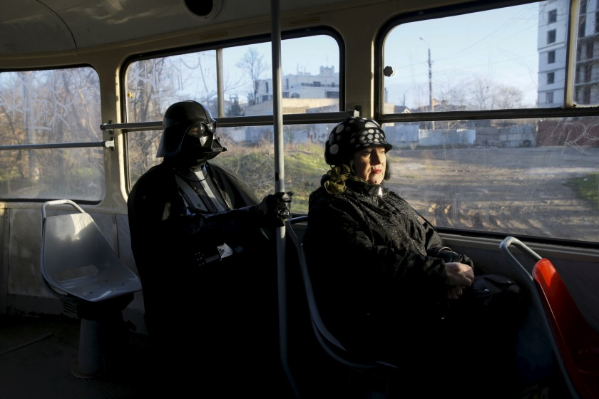 "Darth Mykolaiovych Vader, who is dressed as the Star Wars character Darth Vader, poses for a picture as he rides on a tram in Odessa, Ukraine, December 3, 2015. Darth Vader was bent on galactic domination, but his Ukrainian namesake enjoys more mundane pursuits: local politics, walking the family dog and a spot of embroidery. The Ukrainian citizen, who has changed his name to Darth Mykolaiovych Vader, ran for the post of local mayor in October, his political backers dressed as Stormtroopers. In his trademark black outfit, he is a regular sight around Odessa, a major port city on southern Ukraine's Black Sea coast. REUTERS/Valentyn Ogirenko PICTURE 4 OF 22 - SEARCH ""VALENTYN VADER"" FOR ALL IMAGES - RTX1Y7XW"