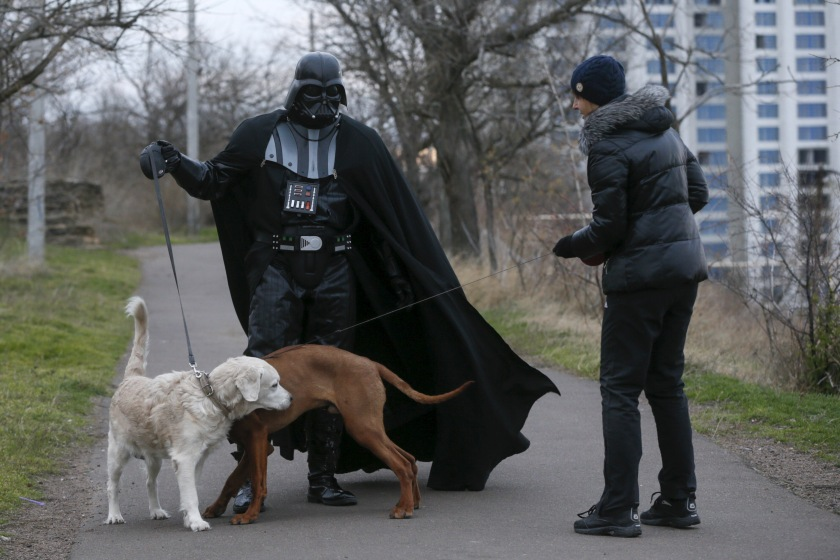 "Darth Mykolaiovych Vader, who is dressed as the Star Wars character Darth Vader, poses for a picture as he speaks to a woman while walking his dog in a park in Odessa, Ukraine, December 3, 2015. Darth Vader was bent on galactic domination, but his Ukrainian namesake enjoys more mundane pursuits: local politics, walking the family dog and a spot of embroidery. The Ukrainian citizen, who has changed his name to Darth Mykolaiovych Vader, ran for the post of local mayor in October, his political backers dressed as Stormtroopers. In his trademark black outfit, he is a regular sight around Odessa, a major port city on southern Ukraine's Black Sea coast. REUTERS/Valentyn Ogirenko PICTURE 3 OF 22 - SEARCH ""VALENTYN VADER"" FOR ALL IMAGES - RTX1Y7XZ"