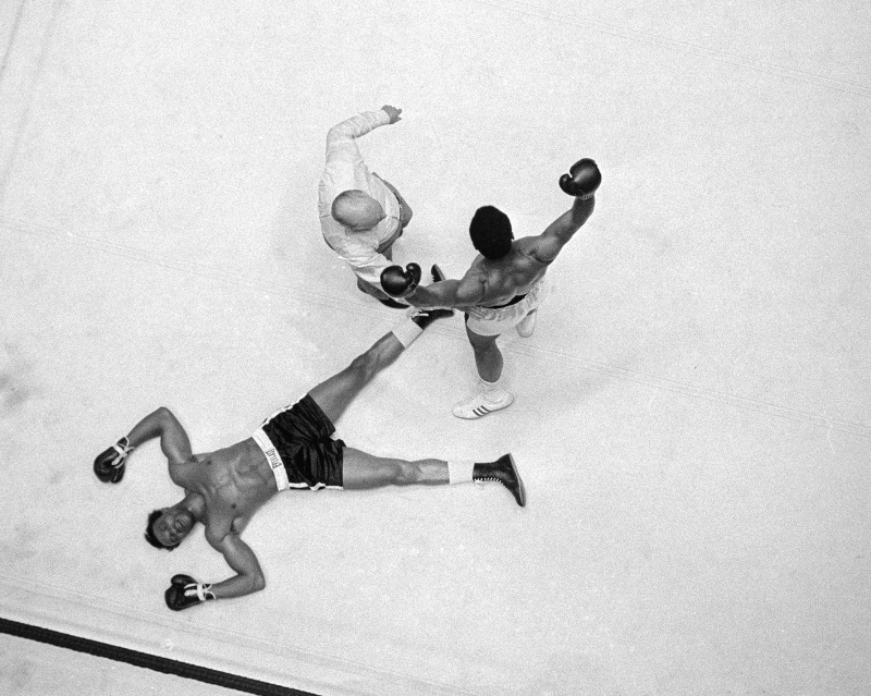 Cleveland Williams is spreadeagled on the canvas as referee Harry Kessler sends Muhammad Ali to a neutral corner during their heavyweight bout at the Astrodome in Houston, Nov. 14, 1966. (AP Photo)