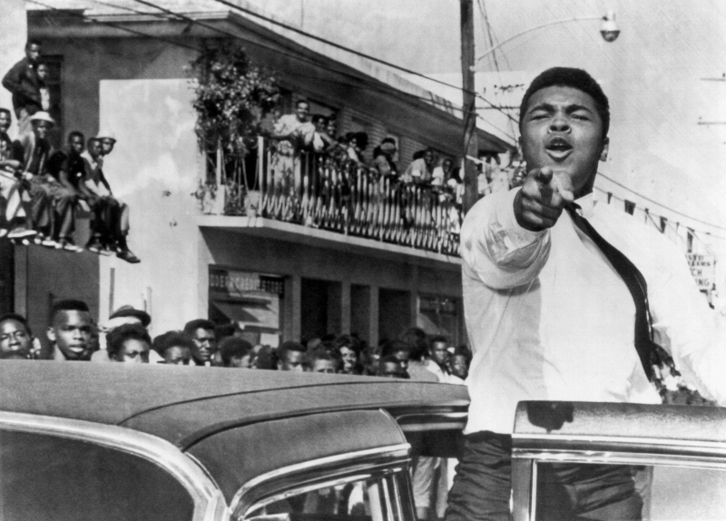 American boxer Cassius Clay (later known as Muhammad Ali) points at the camera from an open car door as he takes part in a pre-football game parade, Miami, Florida, December 14, 1963. He was Miami to train for his title fight against Sonny Liston. (Photo by Underwood Archives/Getty Images)