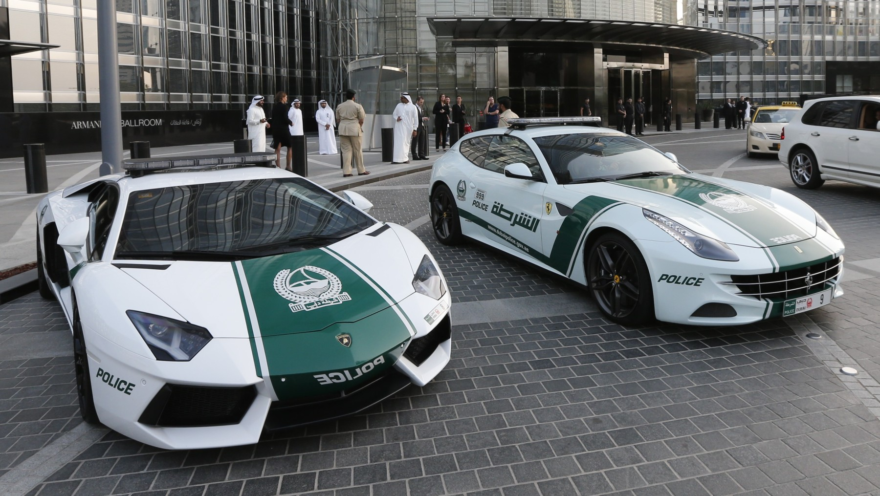 """A picture taken on April 25, 2013 shows Lamborghini (L) and Ferrari police vehicles at the foot of the Burj Khalifa tower in the Gulf emirate of Dubai. Two weeks after introducing the Lamborghini police car, Dubai Police has introduced a Ferrari to the fleet, to further strengthen the """"image of luxury and prosperity"""" of the emirate. AFP  PHOTO /  KARIM SAHIB        (Photo credit should read KARIM SAHIB/AFP/Getty Images)"""