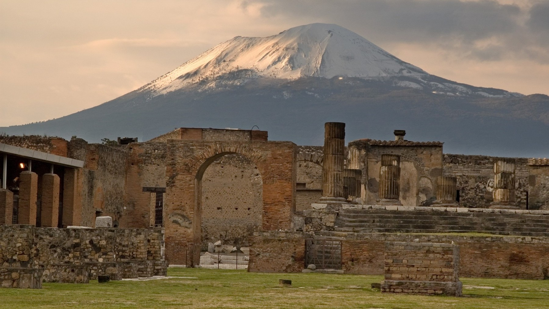 The sun begins to set on the snow capped Mount Vesuvius still overlooking Temple of Jupiter standing in the forum of Pompeii. (DHuss/Creative RF/Getty Images)