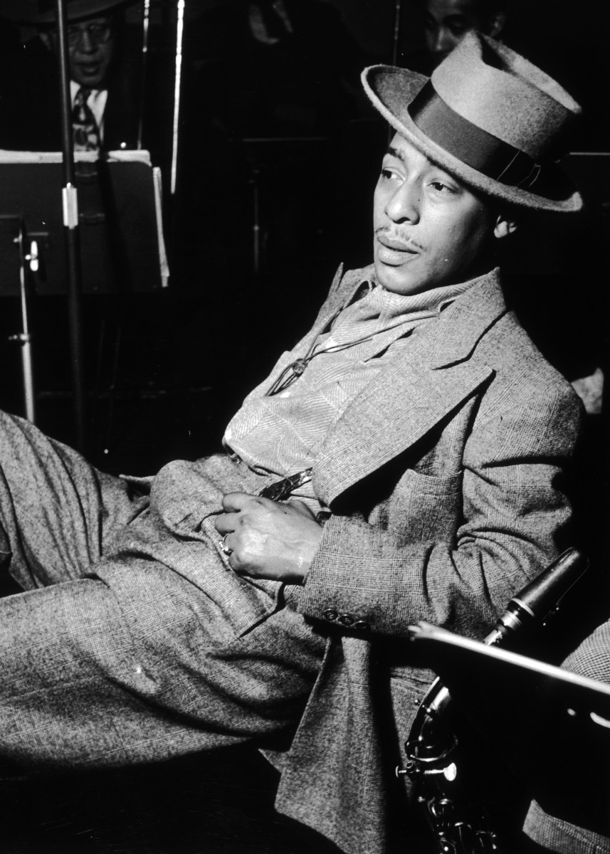 circa 1945:  EXCLUSIVE American jazz saxophonist Johnny Hodges (1907-1970) leans back in a chair with a saxophone resting next to him. Hodges wears a suit and a felt hat.  Other members of the band are seated in the background.  (Photo by Metronome/Getty Images)
