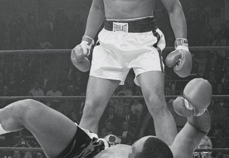 (Original Caption) Lewiston: Heavyweight champion Cassius Clay stands over the downed Sonny Liston and taunts him after knocking him out in the first round of their title match May 25.