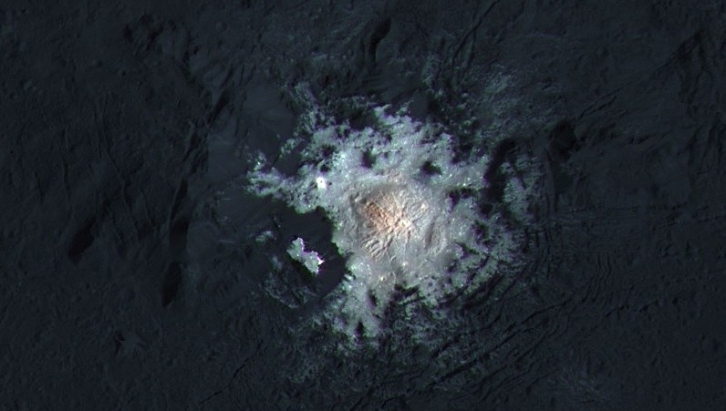 The bright spots of Occator Crater are shown in enhanced color in this view from NASA's Dawn spacecraft. Such views can be used to highlight subtle color differences on Ceres' surface.(NASA/JPL-Caltech/UCLA/MPS/DLR/IDA/PSI/LPI)