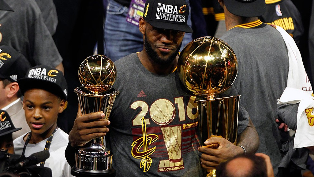June 19, 2016; Oakland, CA, USA; Cleveland Cavaliers forward LeBron James (23) celebrates with the Larry O'Brien championship and Bill Russell MVP trophies following the 93-89 victory against the Golden State Warriors in game seven of the NBA Finals at Oracle Arena. Mandatory Credit: Cary Edmondson-USA TODAY Sports  - RTX2H3O6