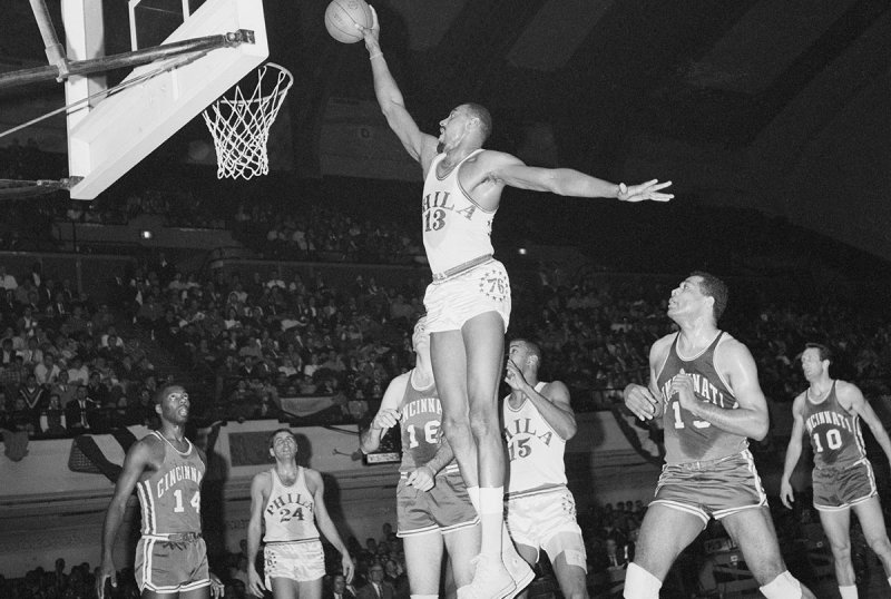 (Original Caption) Philadelphia: 76ers' Wilt Chamberlain, jumps high as Cincinnati Royal, Jerry Lucas (16) and Wayne Embry (15) can only look on during first period action, March 20th at convention hall.
