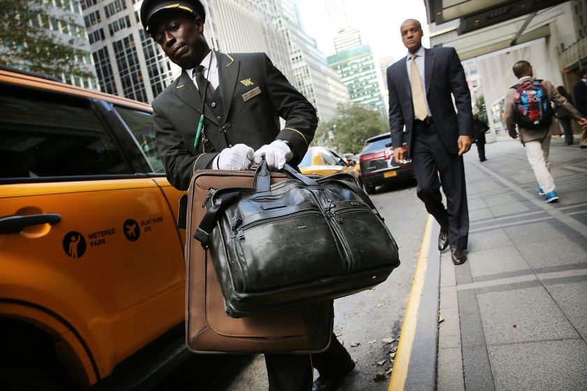 NEW YORK, NY - OCTOBER 06: An employee helps a guest with his bags at the Waldorf Astoria, the landmark New York hotel, is viewed on October 6, 2014 in New York City. It was announced October 6, that Hilton Worldwide will sell the Waldorf to the Beijing-based Anbang Insurance Group for $1.95 billion. As part of the deal the Waldorf will undergo a major renovation. The Park Avenue hotel opened on October 1, 1931, and claimed to be the biggest hotel in the world at the time, attracting movie stars, politicians and the wealthy. (Photo by Spencer Platt/Getty Images)