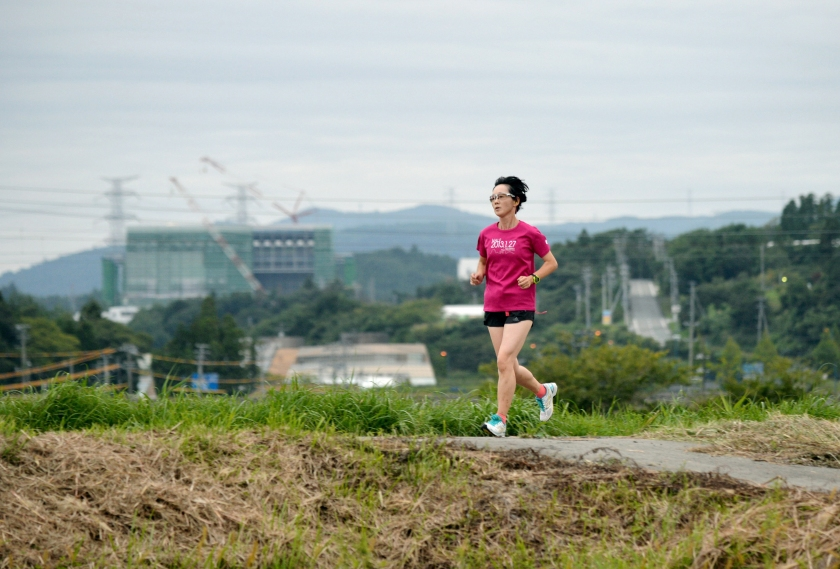 Masae Endo, 50, jogs the town where the evacuation order was lifted on September 5, 2015 in Naraha, Japan. The Fukushima Daini Nuclear Power Plant can be seen in the distance. (The Asahi Shimbun via Getty Images)