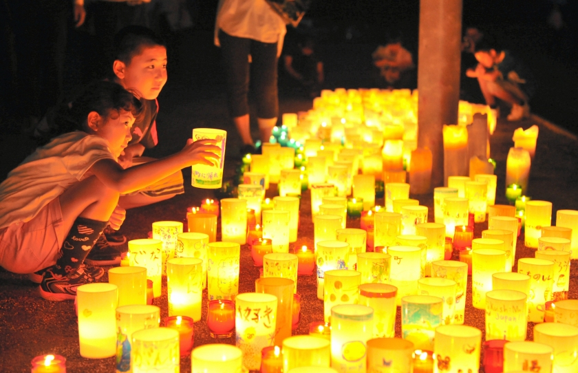 People light candles in pray for restoration as the evacuation order is to be lifted on September 4, 2015 in Naraha, Japan. (The Asahi Shimbun via Getty Images)