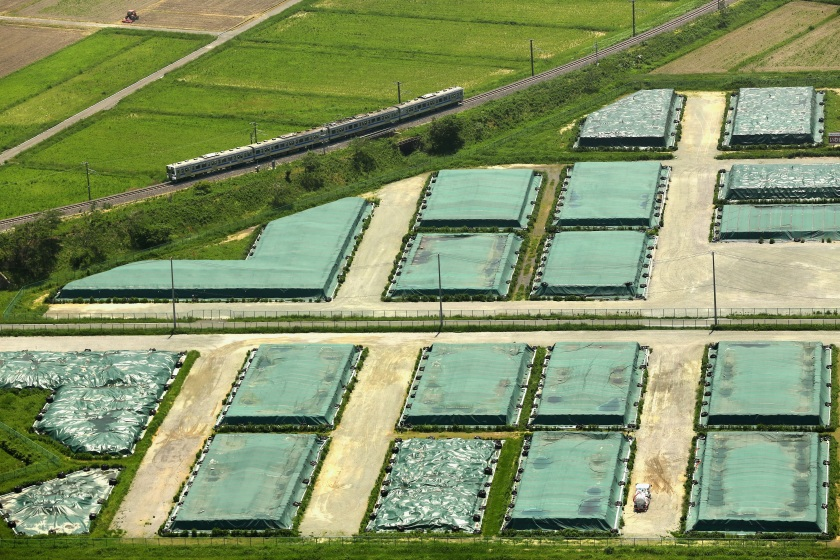 NARAHA, JAPAN - JUNE 01: (CHINA OUT, SOUTH KOREA OUT) In this aerial image, a Joban line train runs past a temporary storage site of the radiation contaiminated soil as the train operation restarted between Hirono and Tatsuno on June 1, 2014 in Naraha, Fukushima, Japan. The government plans to lift the mandatory evacuation order for Naraha, allowing residents to return to the town hit hard by the Fukushima nuclear disaster as early as spring 2015. (Photo by The Asahi Shimbun via Getty Images)