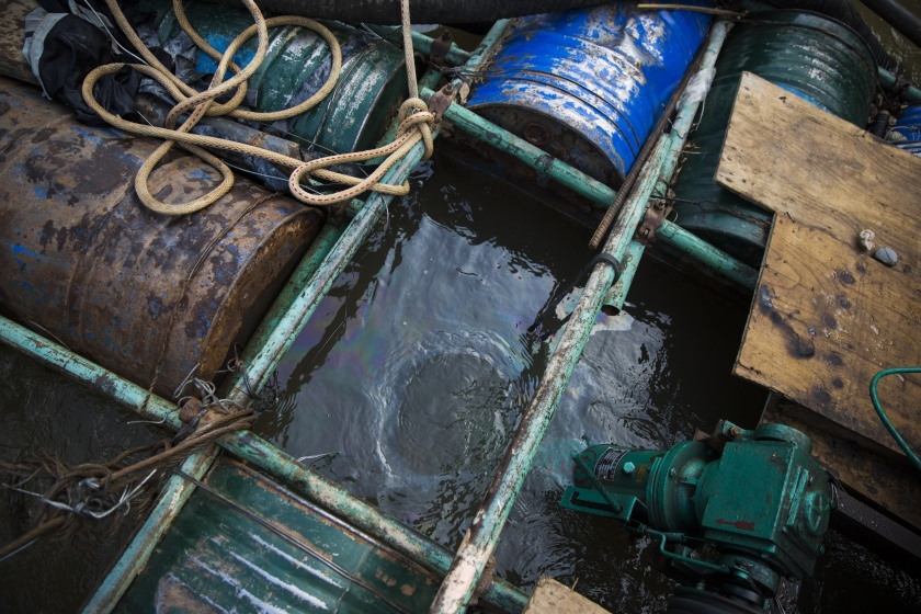 Oil slick floats below a rig at a sand dredging site near Kengtung, Shan State, Myanmar, on Thursday, Feb. 18, 2016. The recently-elected National League for Democracy has been vague about its plans for the country. Its economic platform pledged to do things such as expand the tax base and increase foreign investment, without saying how. (Taylor Weidman/Bloomberg via Getty Images)