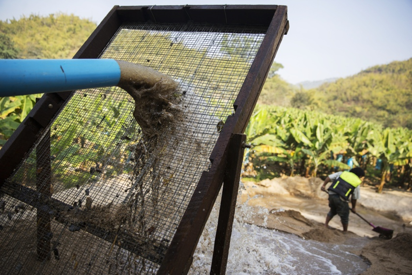 Slurry from a makeshift pipeline pours through a filter on the banks of a river at a sand dredging site near Kengtung, Shan State, Myanmar, on Thursday, Feb. 18, 2016. The recently-elected National League for Democracy has been vague about its plans for the country. Its economic platform pledged to do things such as expand the tax base and increase foreign investment, without saying how. (Taylor Weidman/Bloomberg via Getty Images)