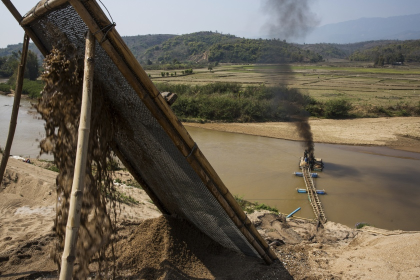 Slurry pours through a filter from a makeshift pipeline on the banks of a river as smoke billows from the rig at a sand dredging site near Kengtung, Shan State, Myanmar, on Thursday, Feb. 18, 2016. The recently-elected National League for Democracy has been vague about its plans for the country. Its economic platform pledged to do things such as expand the tax base and increase foreign investment, without saying how. (Taylor Weidman/Bloomberg via Getty Images)
