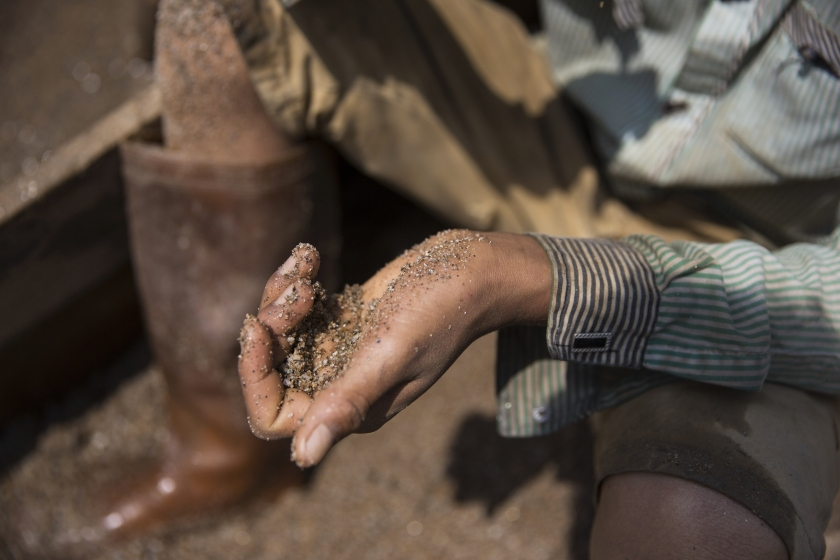 A worker holds a handful of sand on the banks of a river at a sand dredging site near Kengtung, Shan State, Myanmar, on Thursday, Feb. 18, 2016. The recently-elected National League for Democracy has been vague about its plans for the country. Its economic platform pledged to do things such as expand the tax base and increase foreign investment, without saying how. (Taylor Weidman/Bloomberg via Getty Images)