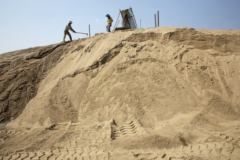 Slurry pours through a filter from a makeshift pipeline as workers shovel sand at a sand dredging site near Kengtung, Shan State, Myanmar, on Thursday, Feb. 18, 2016. The recently-elected National League for Democracy has been vague about its plans for the country. Its economic platform pledged to do things such as expand the tax base and increase foreign investment, without saying how. (Taylor Weidman/Bloomberg via Getty Images)