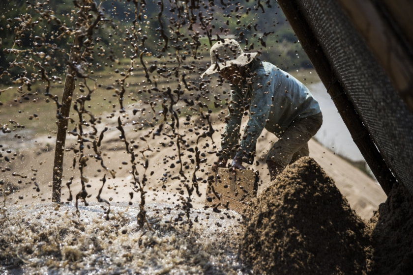 A worker directs the flow of slurry from a makeshift pipeline pouring through a filter on the banks of a river at a sand dredging site near Kengtung, Shan State, Myanmar, on Thursday, Feb. 18, 2016. The recently-elected National League for Democracy has been vague about its plans for the country. Its economic platform pledged to do things such as expand the tax base and increase foreign investment, without saying how. (Taylor Weidman/Bloomberg via Getty Images)