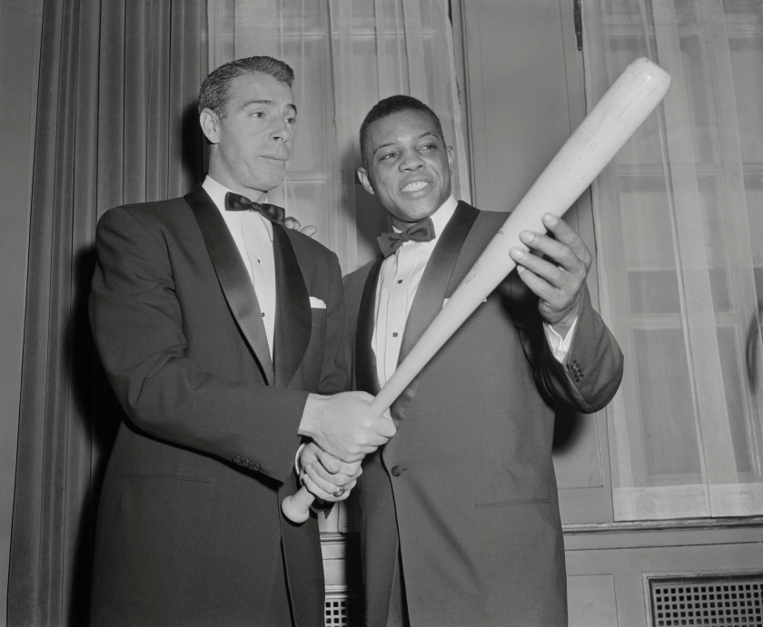 """(Original Caption) Joe DiMaggio, (L) who was just voted to Baseball's Hall of Fame, passes on a few batting tips to Willie Mays, who's a slugger in his own right. Their meeting occurred at the 32nd Annual dinner of the Baseball Writers at the Waldorf Astoria tonight. Mays, Giant outfielder and last year's NL MVP, won the Scribes' Sid Mercer Award as """"Player of The Year."""" His batting average last year was .345. He hit 41 homers and has a slugging average of .667."""