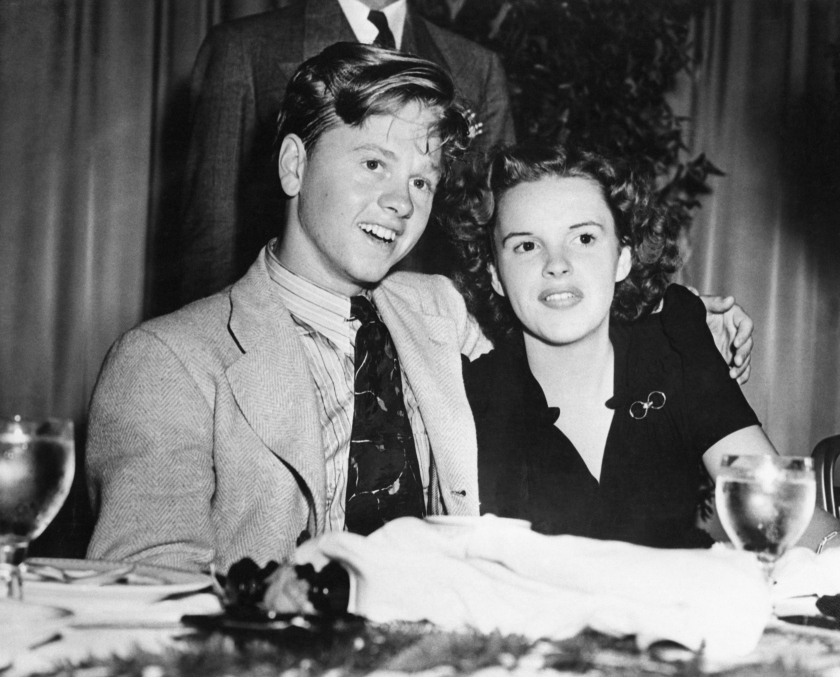 Judy Garland and Mickey Rooney, young screen stars here for personal appearances, are pictured in the Empire Room of the Waldorf-Astoria, Aug. 16th, where they had luncheon with a welcoming committee of 300 of their young loyal fans from various neighborhoods of New York City.