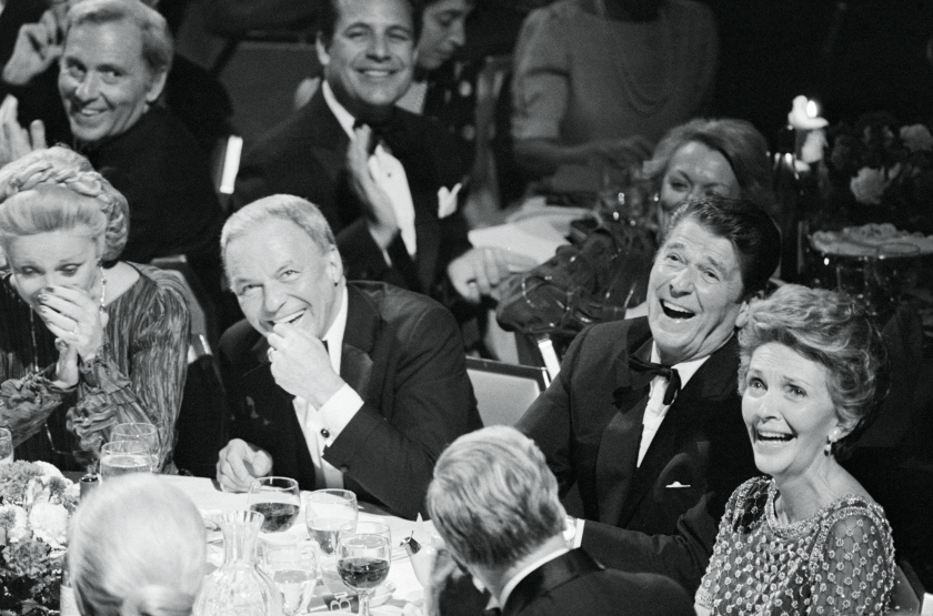 """(Original Caption) Frank and Ron. New York: Frank Sinatra (left) and Ronald and Nancy Reagan share a laugh at a Republican """"victory dinner"""" at New York's Waldorf Astoria. The affair was one of 19 $1,000-a-plate fund-raising affairs being held across the country. A closed-circuit television network emanating from three cities was set up to provide part of the program for all 19 cities."""