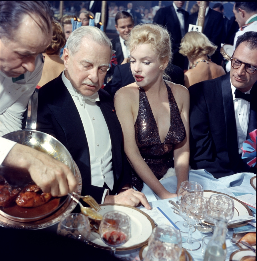 A waiter serves food to American finacier Winthrop Aldridge (1885 - 1974), who sits beside married couple, actress Marilyn Monroe (born Norma Jeane Mortenson, 1926 - 1962) and playwright Arthur Miller (1915 - 2005), during the 'April in Paris Ball' at the Waldorf Astoria, New York, New York, April 11, 1957. (Photo by Peter Stackpole/The LIFE Picture Collection/Getty Images)