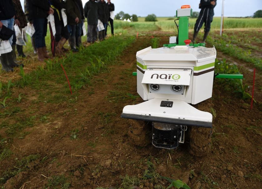 "Farmers look at a weeding robot during a demonstration of new technologies ""Digifermes"" (Digital farms) at the Arvalis farm, an applied agricultural research organisation dedicated to arable crops. (Jean-Christophe Verhaegen/AFP/Getty Images)"