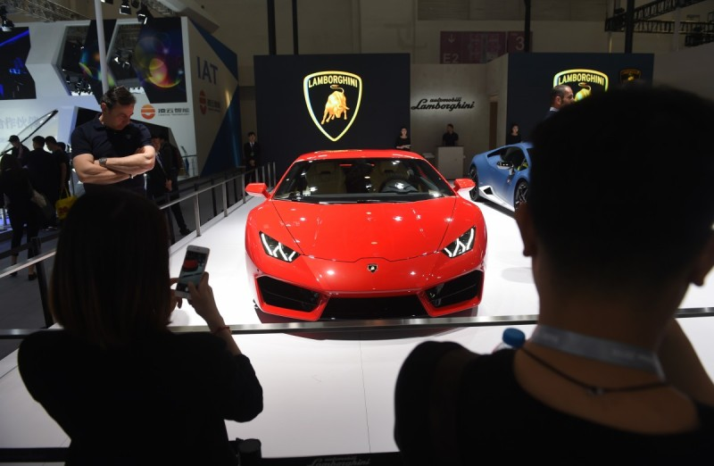 Visitors look at a Lamborghini Huracan LP 580-2 at the Beijing Auto Show in Beijing on April 26, 2016. Global carmakers have gathered in Beijing, to show off their wares as competition intensifies and growth slows in the world's biggest auto market, with the key SUV and new energy vehicle sectors the focus of attention. / AFP / GREG BAKER (Photo credit should read GREG BAKER/AFP/Getty Images)