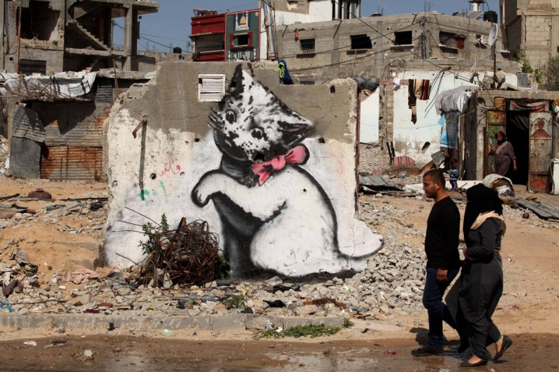 BEIT HANOUN, GAZA - FEBRUARY 27: People pass by a graffiti on a wall of a building drawn by British artist Banksy in Beit Hanoun, Gaza on February 27, 2015. Famous British artist Banksy visited Gaza and drew graffiti on the walls of houses in Beit Hanoun destroyed in Israel's recent attacks on Gaza. (Photo by Ashraf Amra/Anadolu Agency/Getty Images)
