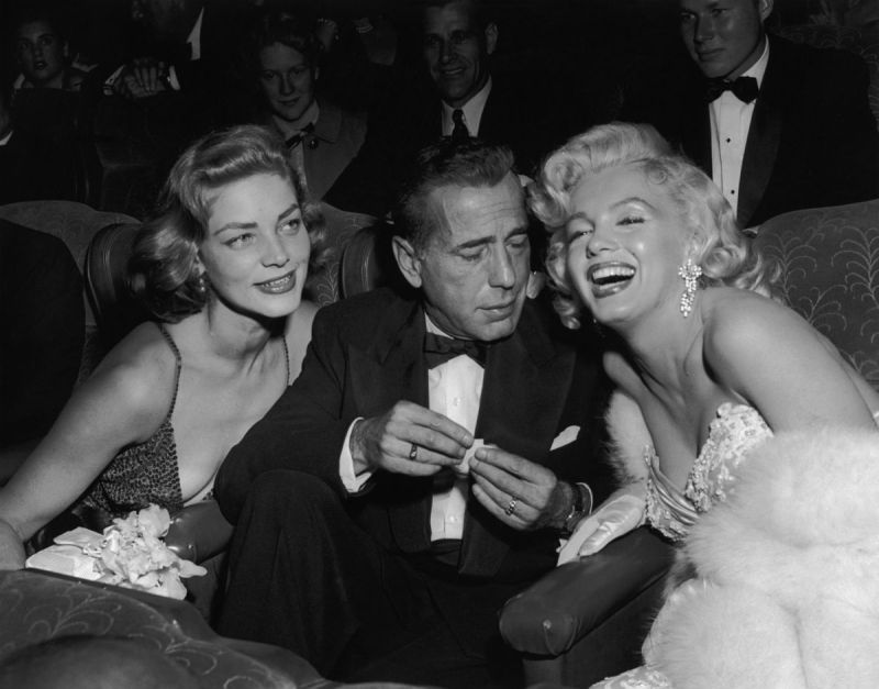 1953: EXCLUSIVE Married American actors Lauren Bacall (L) and Humphrey Bogart (1899 - 1957) pose with American actor Marilyn Monroe (1926 - 1962) at the premiere of director Jean Negulesco's film, 'How to Marry a Millionaire'. Bacall and Monroe costarred in the film. (Photo by Darlene Hammond/Hulton Archive/Getty Images)