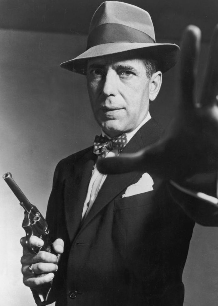 1951: American actor Humphrey Bogart carrying a gun and holding out his hand, in a still from director Bretaigne Windust's film, 'The Enforcer'. (Photo by American Stock/Getty Images)