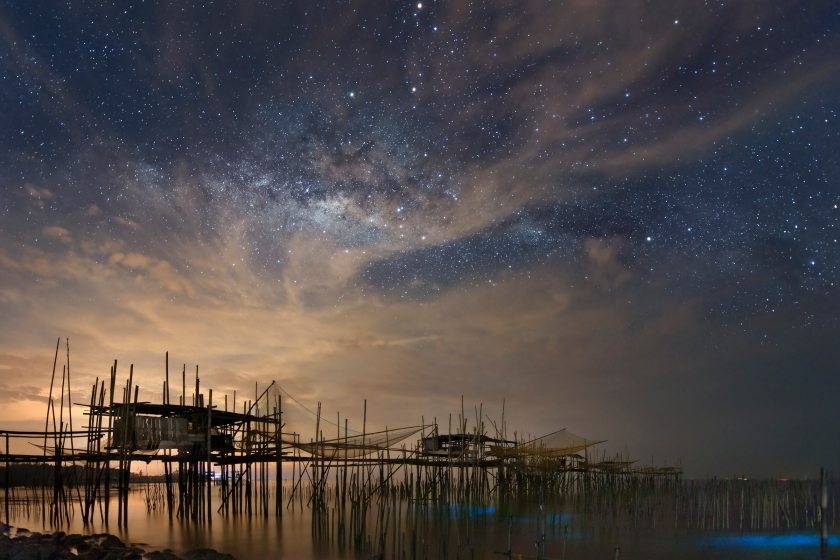 The natural light of the Milky Way battles with the light pollution over the fishing village, or kelong, in Batu Pahat, Malaysia. In the lower right hand corner, there is also bioluminescence in the waters at the bottom of the kelong. (Yuyu Wang)