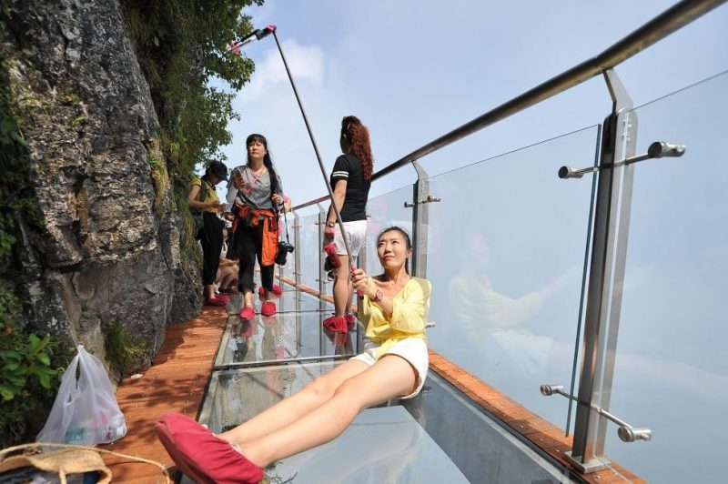 ZHANGJIAJIE, CHINA - AUGUST 01: A tourist takes a selfie on the 100-meter-long and 1.6-meter-wide glass skywalk clung the cliff of Tianmen Mountain (or Tianmenshan Mountain) in Zhangjiajie National Forest Park on August 1, 2016 in Zhangjiajie, Hunan Province of China. The Coiling Dragon Cliff skywalk, featuring a total of 99 road turns, layers after another, is the third glass skywalk on the Tianmen Mountain (or Tianmenshan Mountain). (Photo by VCG/VCG via Getty Images)