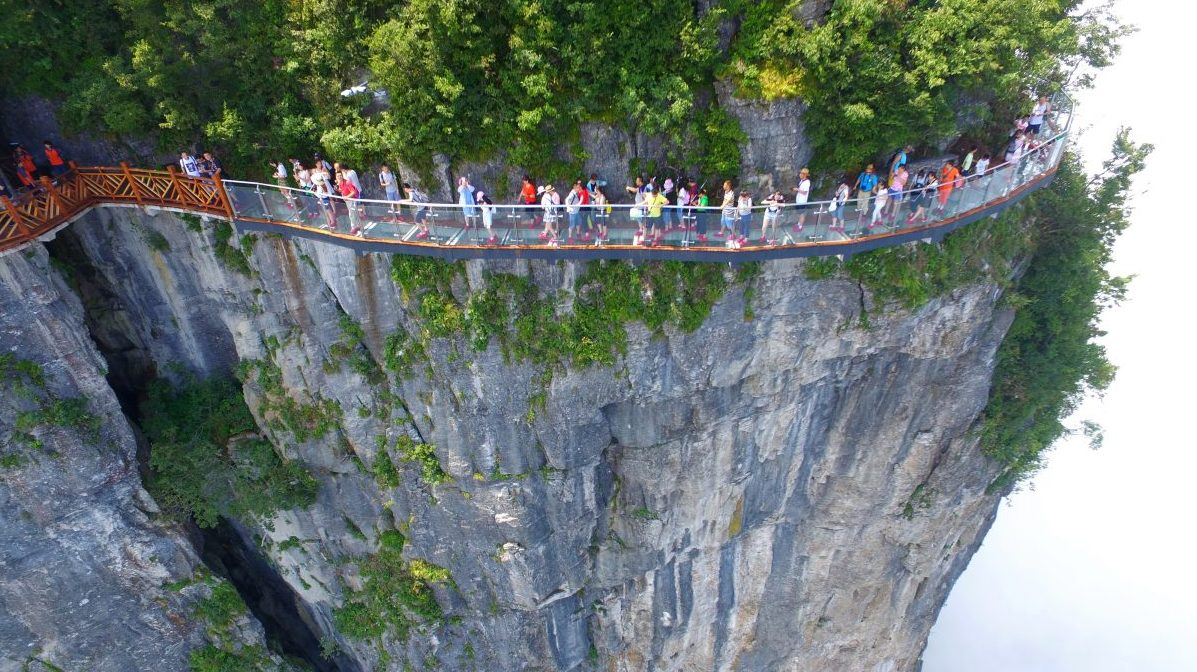 ZHANGJIAJIE, CHINA - AUGUST 01:  Aerial view of tourists walking on the 100-meter-long and 1.6-meter-wide glass skywalk clung the cliff of Tianmen Mountain (or Tianmenshan Mountain) in Zhangjiajie National Forest Park on August 1, 2016 in Zhangjiajie, Hunan Province of China. The Coiling Dragon Cliff skywalk, featuring a total of 99 road turns, layers after another, is the third glass skywalk on the Tianmen Mountain (or Tianmenshan Mountain).  (Photo by VCG/VCG via Getty Images)