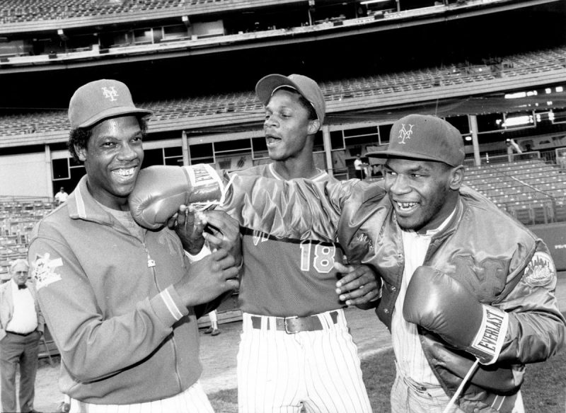 UNITED STATES - SEPTEMBER 10: New York Mets' Dwight Gooden laughs off a right from heavyweight Mike Tyson as referee Darryl Strawberry supervises the event at Shea Stadium. (Photo by Vincent Riehl/NY Daily News Archive via Getty Images)