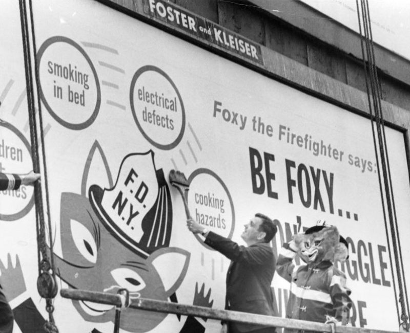 What Smokey the Bear is to the prevention of forest fires, City officials hope Foxy the Fireman will be to human safety. Fire Commissioner Thompson (c) puts the finishing touches to one of 250 billboard signs posted around the city to warn against home fire hazarsd. Looking on are Asst. Chief Charles McKeogh (l) and Foxy himself, played by fireman Barney Schmeltzer. (Photo by William Jacobellis/New York Post Archives / (c) NYP Holdings, Inc. via Getty Images)