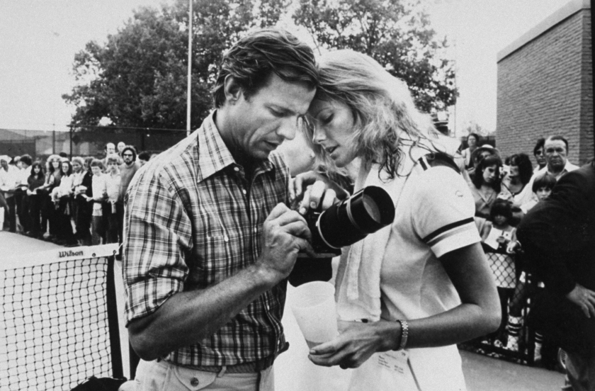 Photographer Peter Beard (L) holding camera with model/wife Cheryl Tiegs (R) on tennis court, as crowd watches behind fence. (Robin Platzer/Twin Images/The LIFE Images Collection/Getty Images)