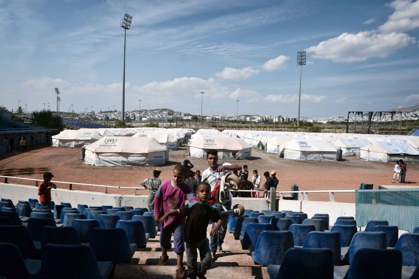 A family walks in the former Helliniko Olympic complex used as refugee camp for mainly Afghani refugees on May 10, 2016 in Athens southern suburb. (Louisa Gouliamaki/AFP/Getty Images)